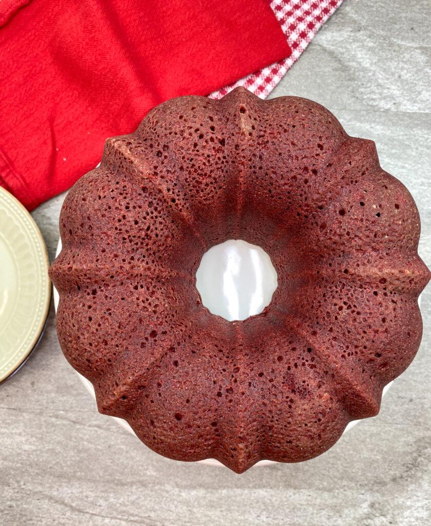 Red velvet bundt cake on a white cake pedestal.