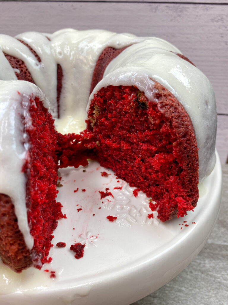 Red velvet bundt cake with cream cheese frosting on a beige plate.