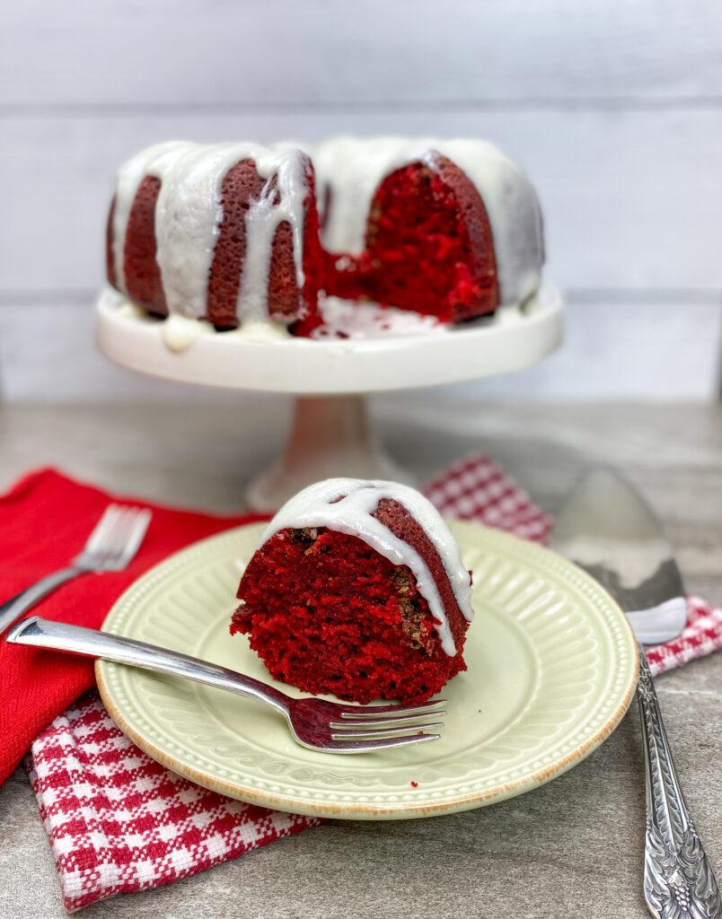 Red velvet bundt cake on a plate and a cake pedestal.