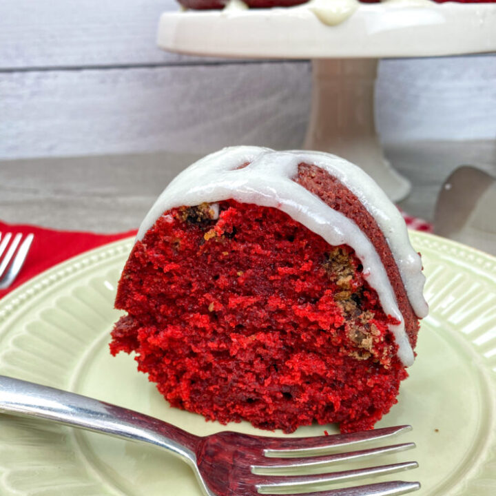 A slice of red velvet bundt cake with cream cheese frosting on a plate.