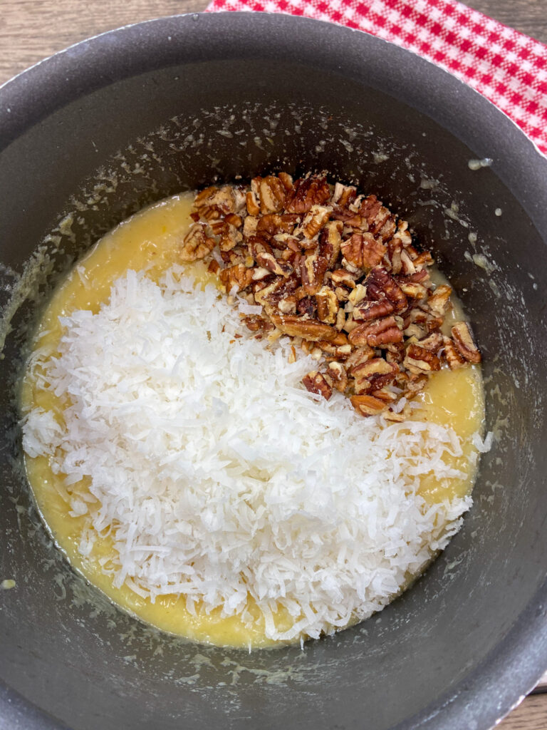 Shredded coconut and chopped pecans in a saucepan.