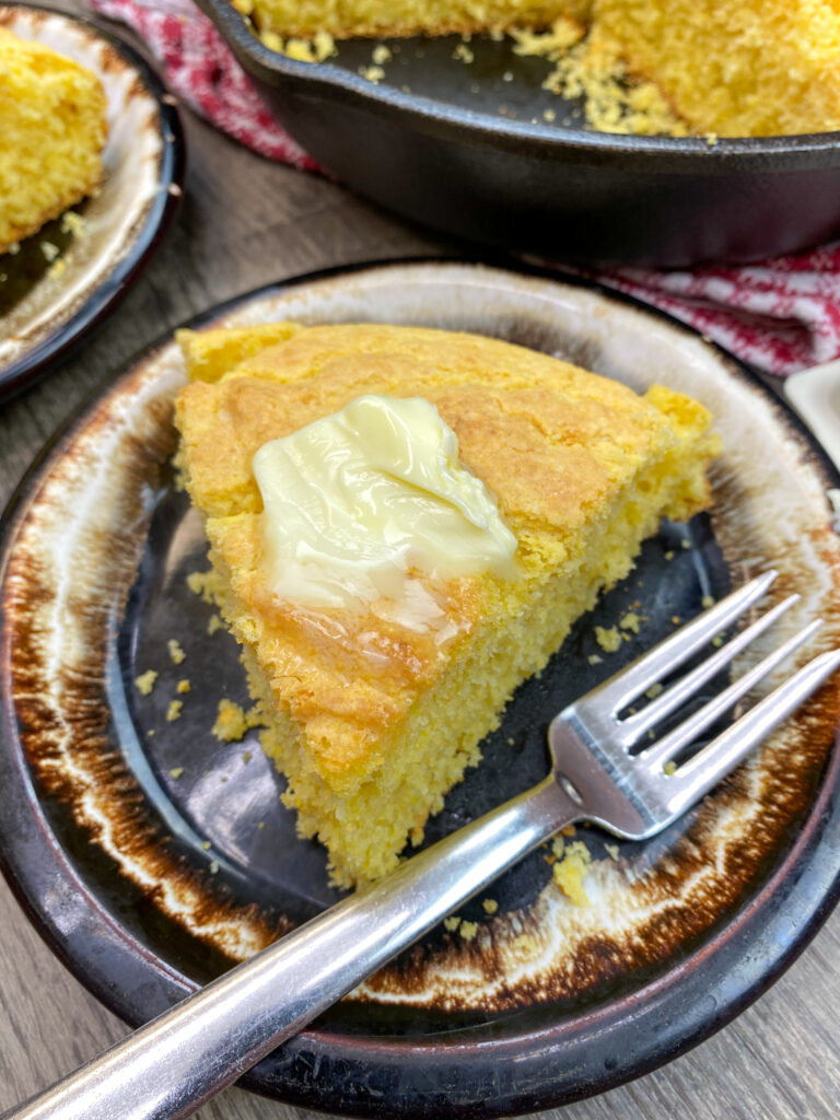 A slice of cornbread topped with butter.