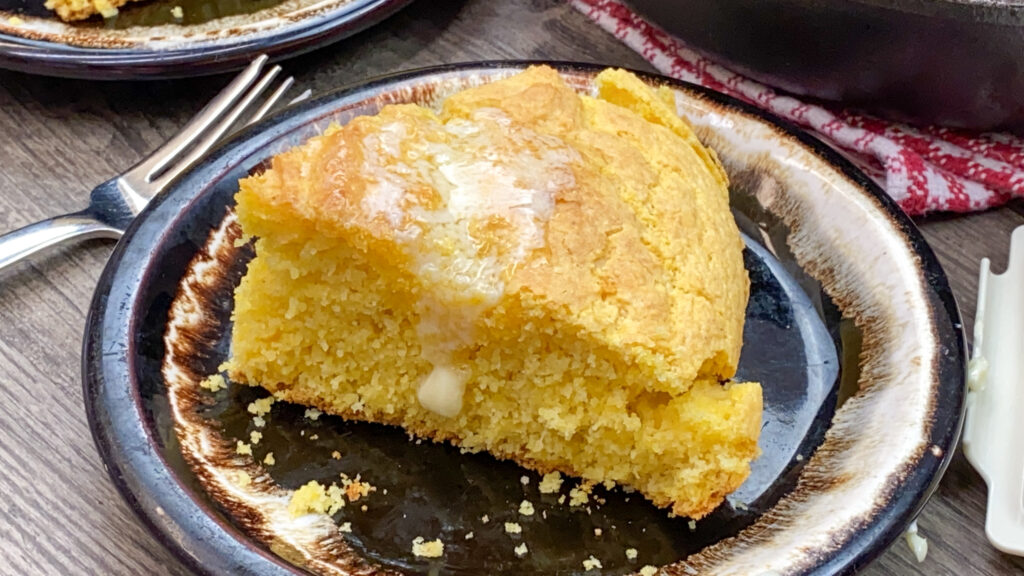 A slice of cornbread on a brown plate with butter on top.