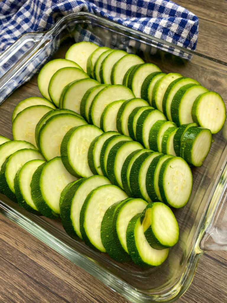 Sliced zucchini in a square baking dish.