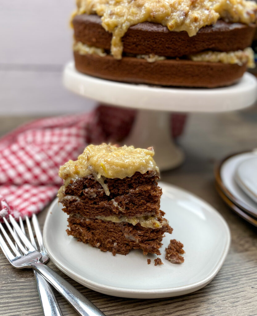 German chocolate cake sliced and on a white plate.