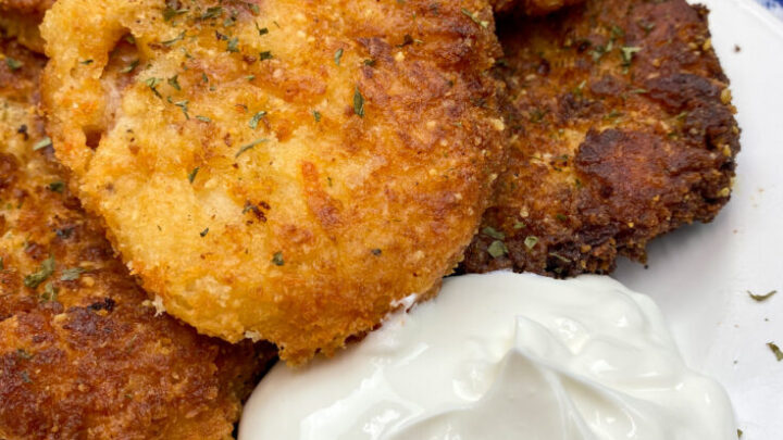 Mashed potato cakes on a plate with sour cream.