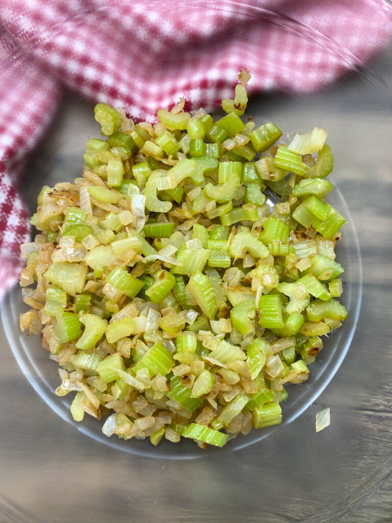 Cooked celery and onions in a glass bowl.