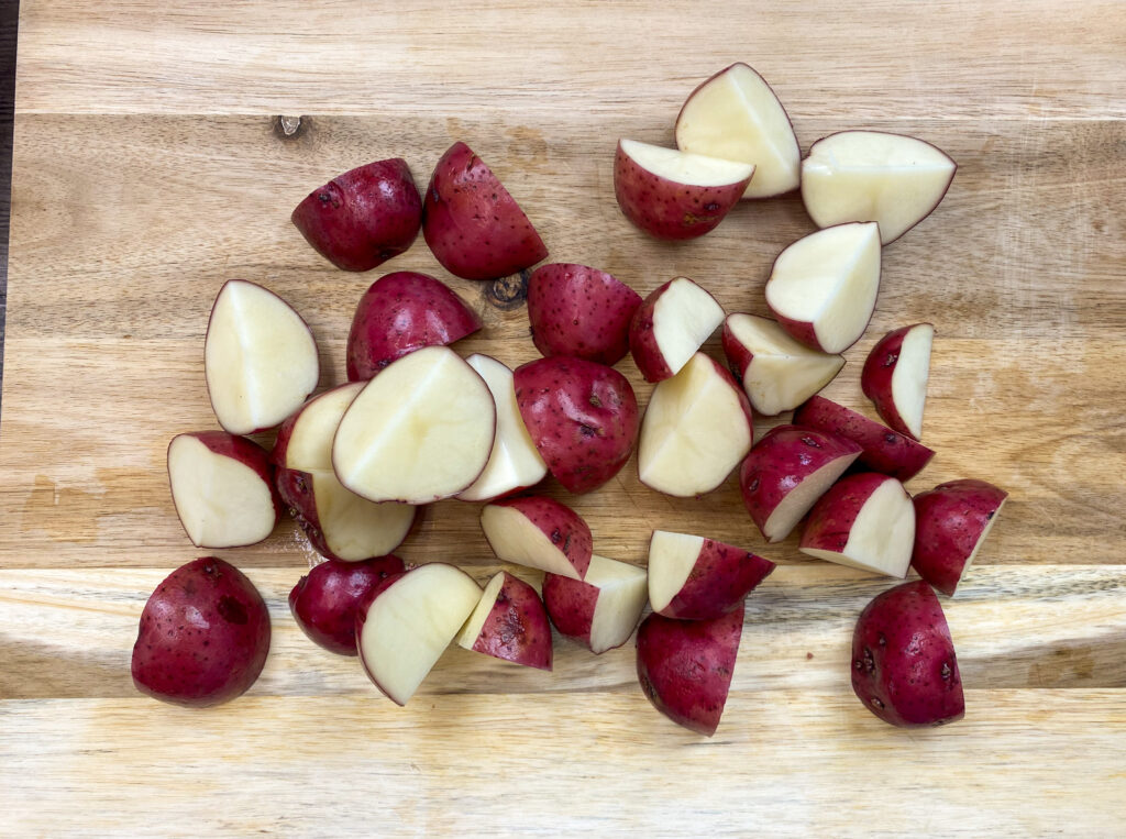 Sliced red potatoes on a wooden cutting board.