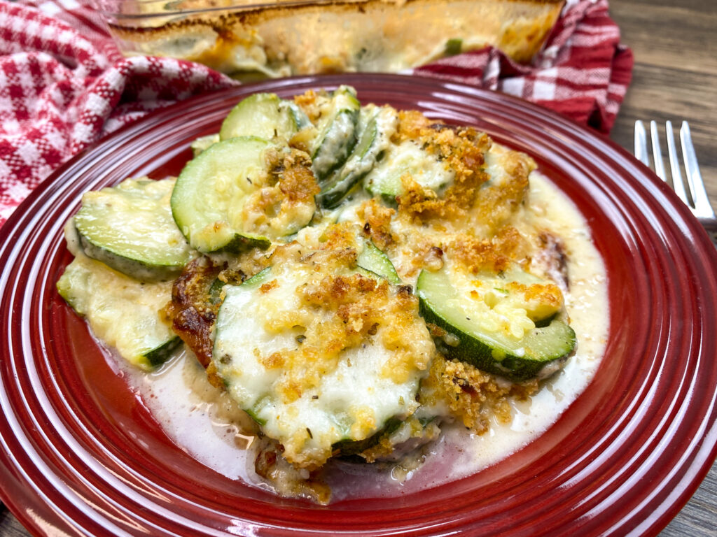 Zucchini casserole on a red plate.