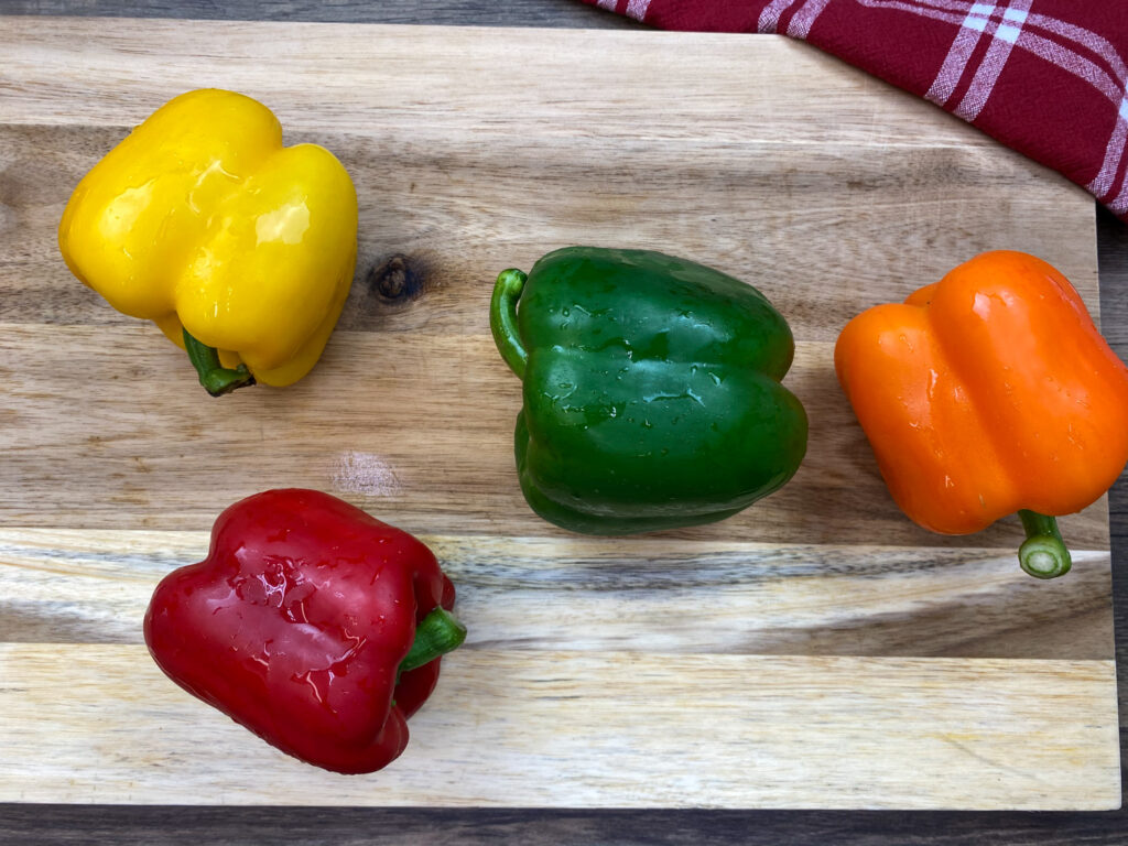 Fresh bell peppers on a cutting board.