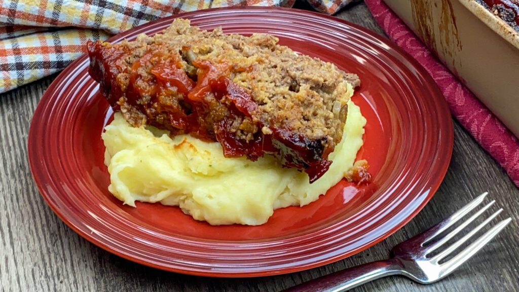 A slice of meatloaf with ketchup on top of mashed potatoes on a red plate.
