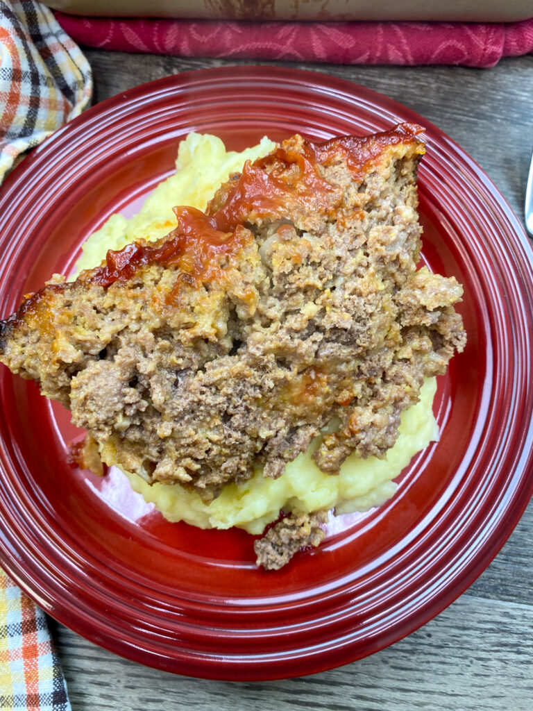 Meatloaf with ketchup on a red plate with mashed potatoes.