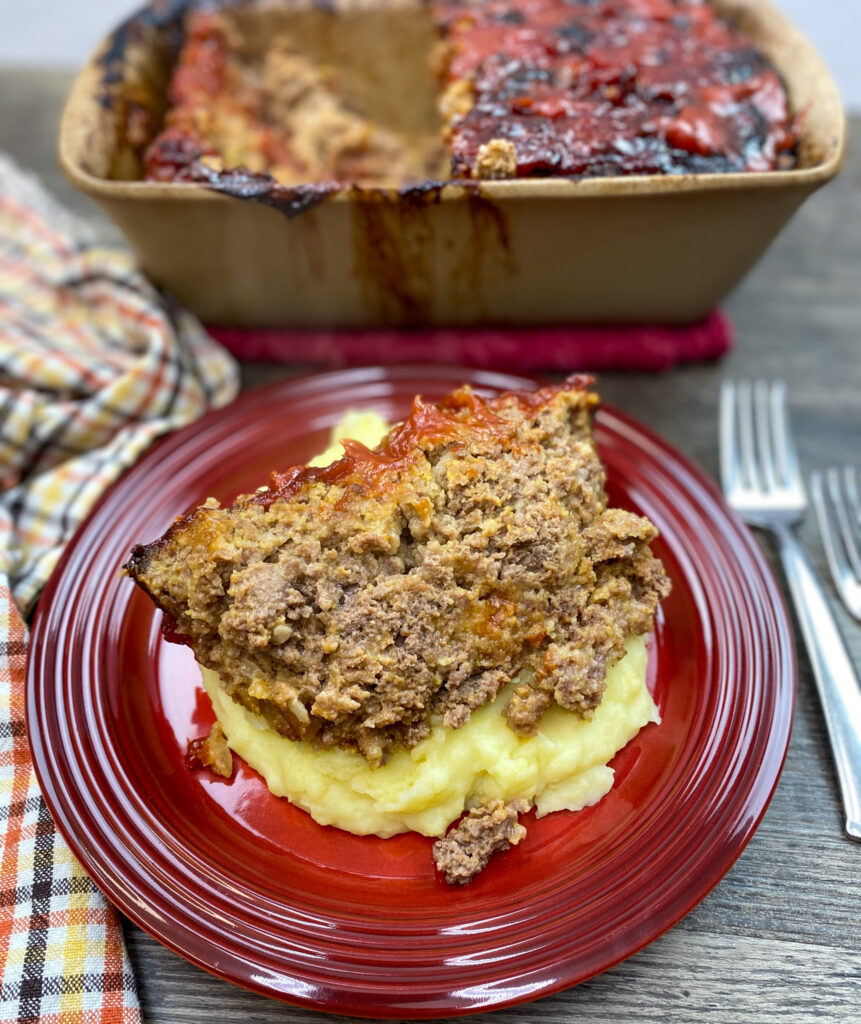 Traditional meatloaf recipe on a red plate with mashed potatoes.