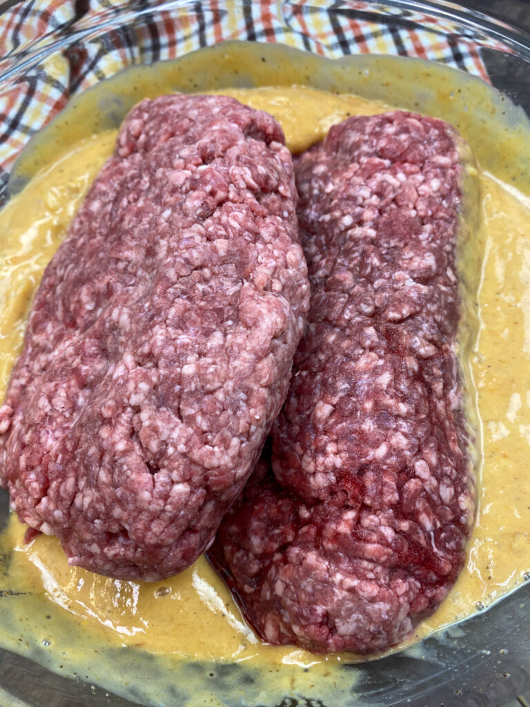 Ground beef in a bowl with meatloaf ingredients.