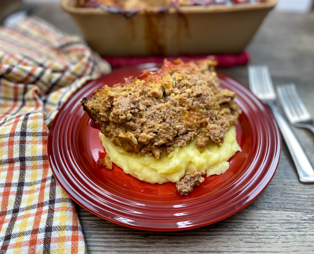 A slice of meatloaf on top of mashed potatoes.