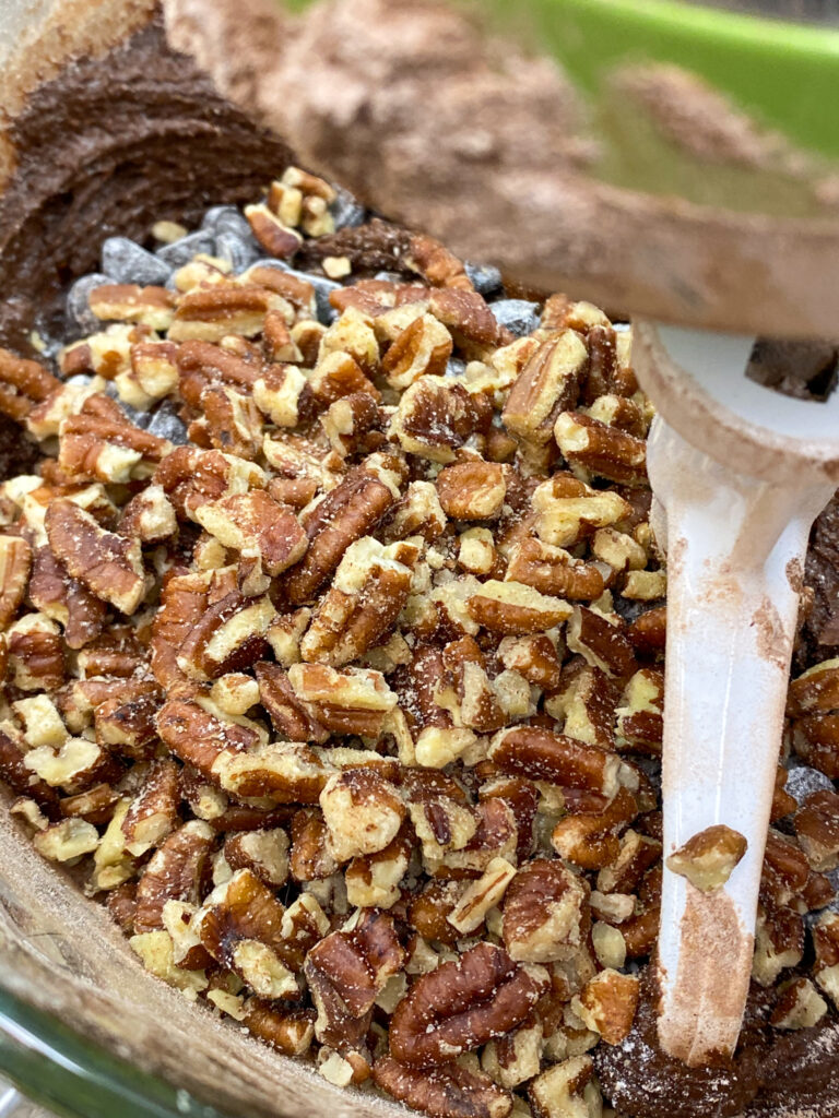 Chopped pecans in a bowl with brownie batter.