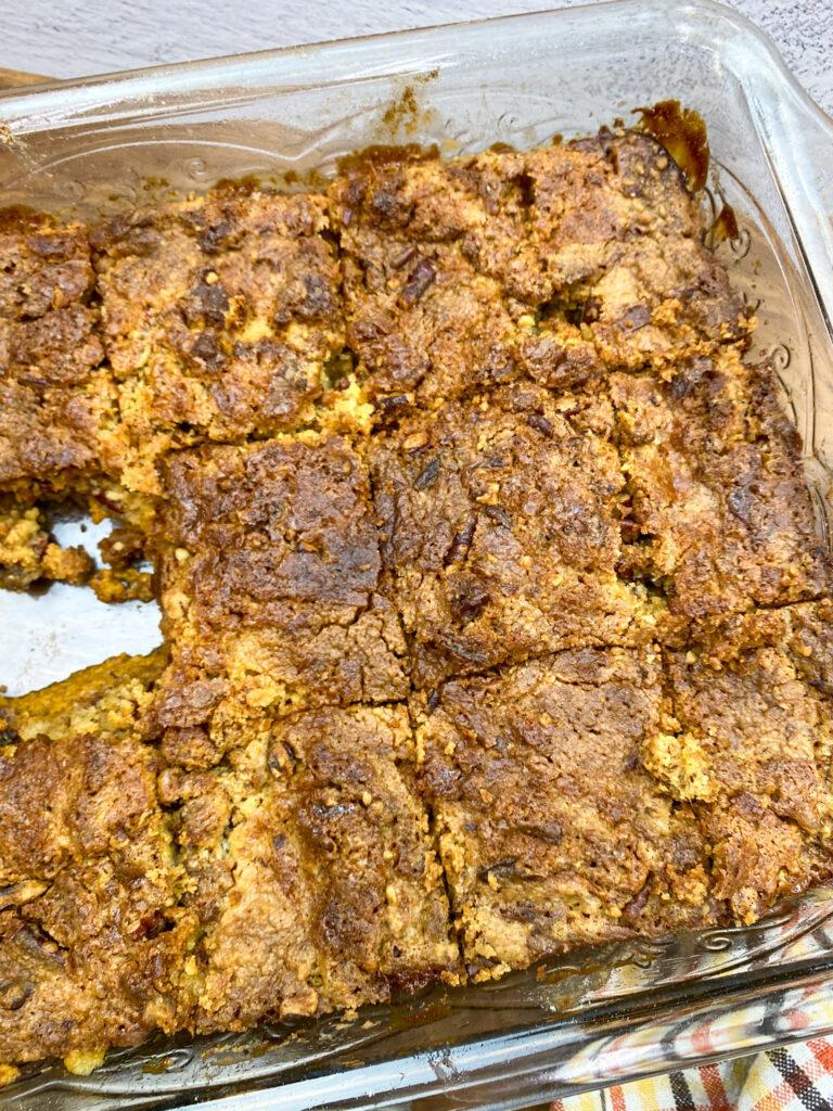 Pumpkin dump cake slices in a pan.
