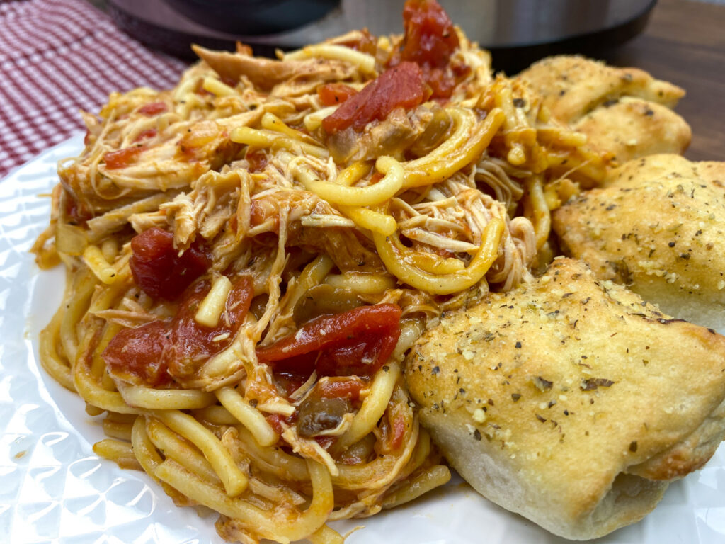 Italian chicken on a plate with breadsticks.