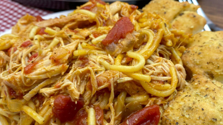 Italian chicken with spaghetti noodles and cheese bread on the side.