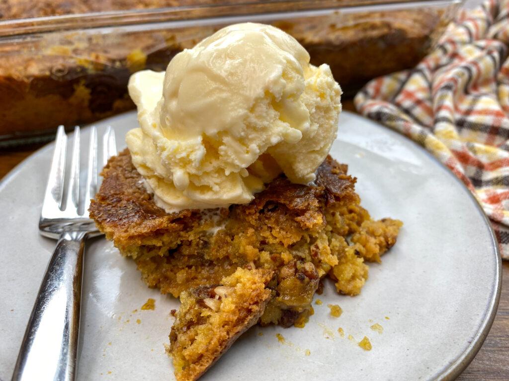 A slice of pumpkin dump cake on a plate with vanilla ice cream.