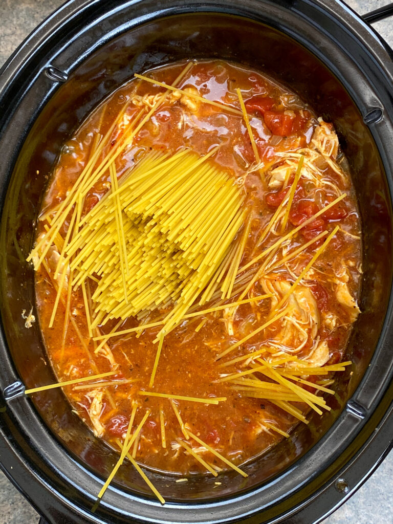 Adding spaghetti noodles to the Crock Pot in an Italian chicken dish,.