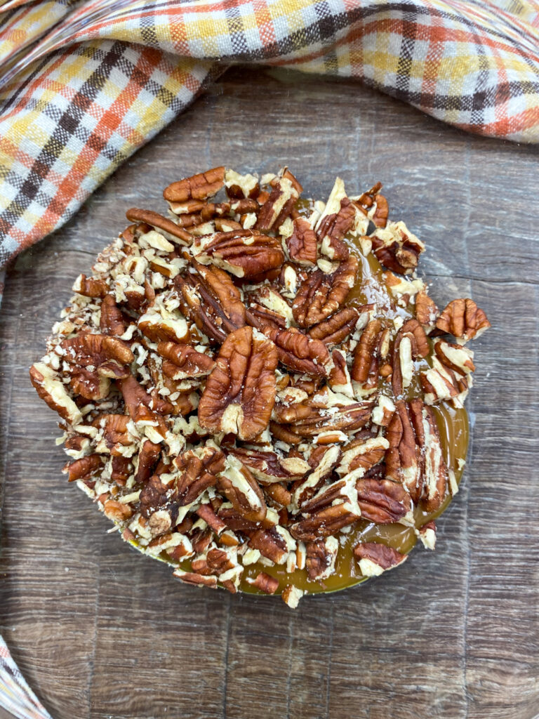 Caramel and chopped pecans in a glass bowl.