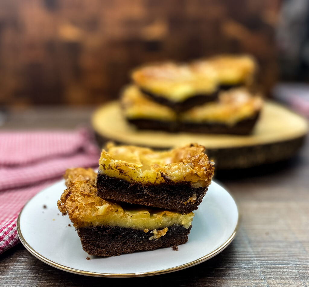 Chocolate chess squares stacked on top of each other on a plate.