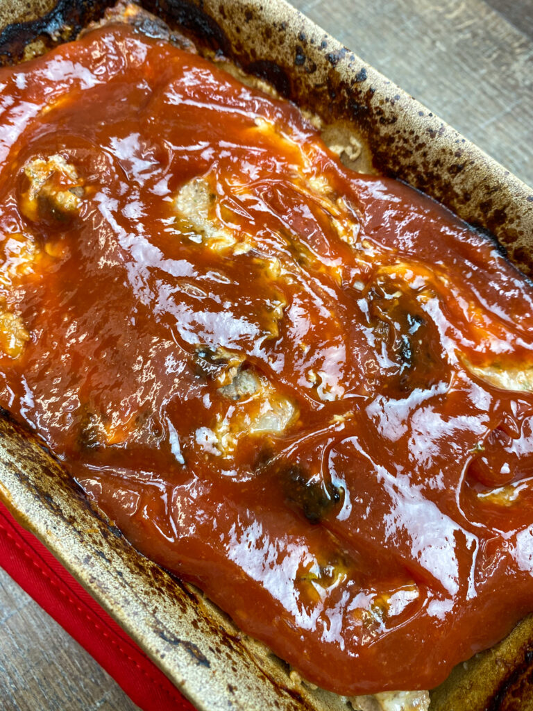 Topping meatloaf with a ketchup mixture.