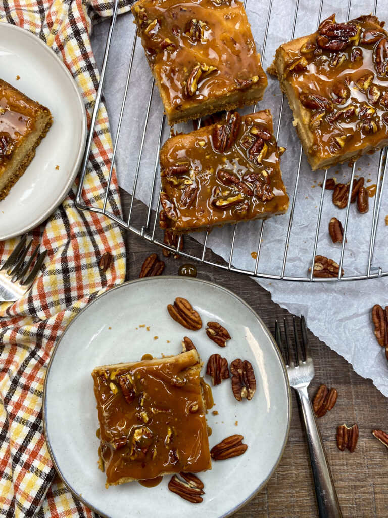 Caramel praline cheesecake squares on a plate.