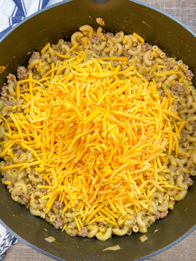 Shredded cheddar cheese in a pan with noodles and beef.