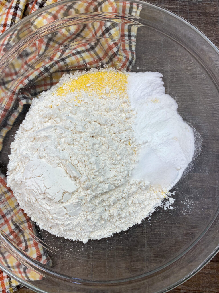 Cornmeal, flour, and baking soda in a glass bowl.