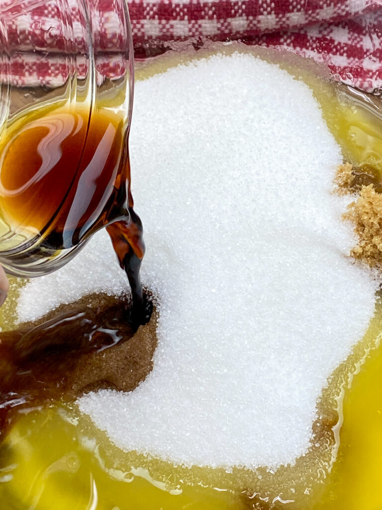 Pouring vanilla extract into a bowl.