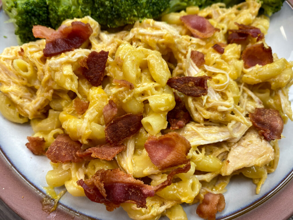 Macaroni noodles with cheese and bacon on  a plate.