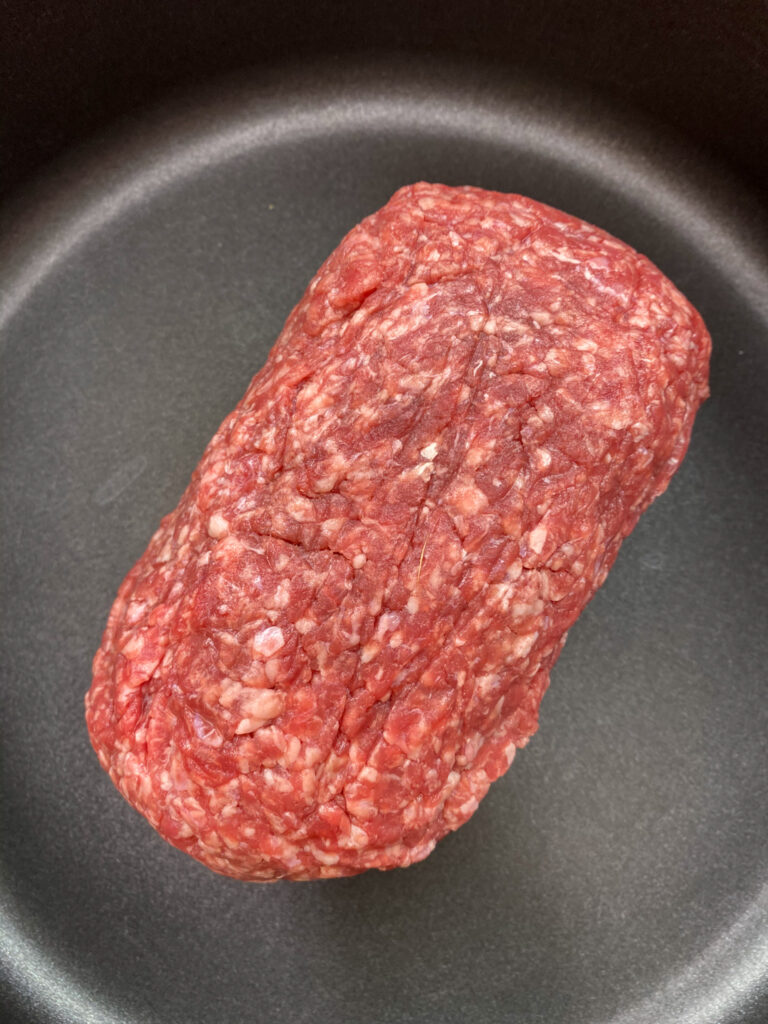 Raw ground beef in a skillet.