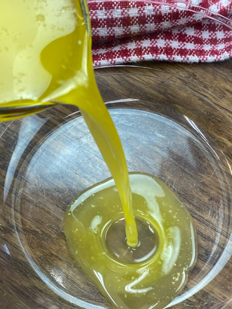 Pouring melted butter in to a large bowl.