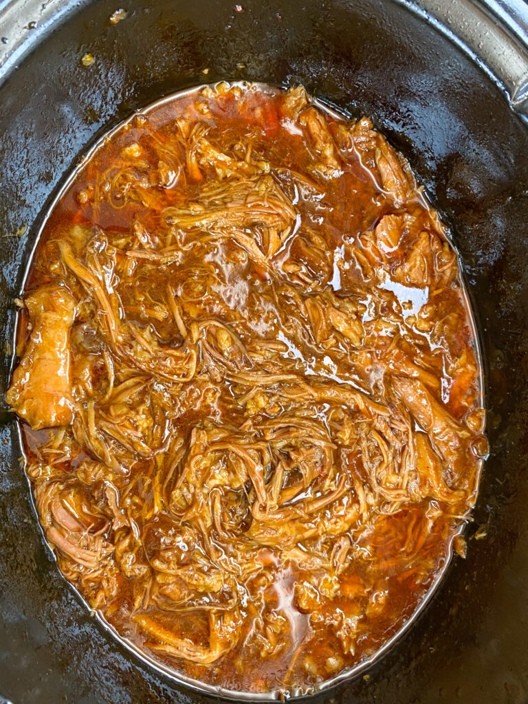 Cooked pulled pork in the slow cooker.