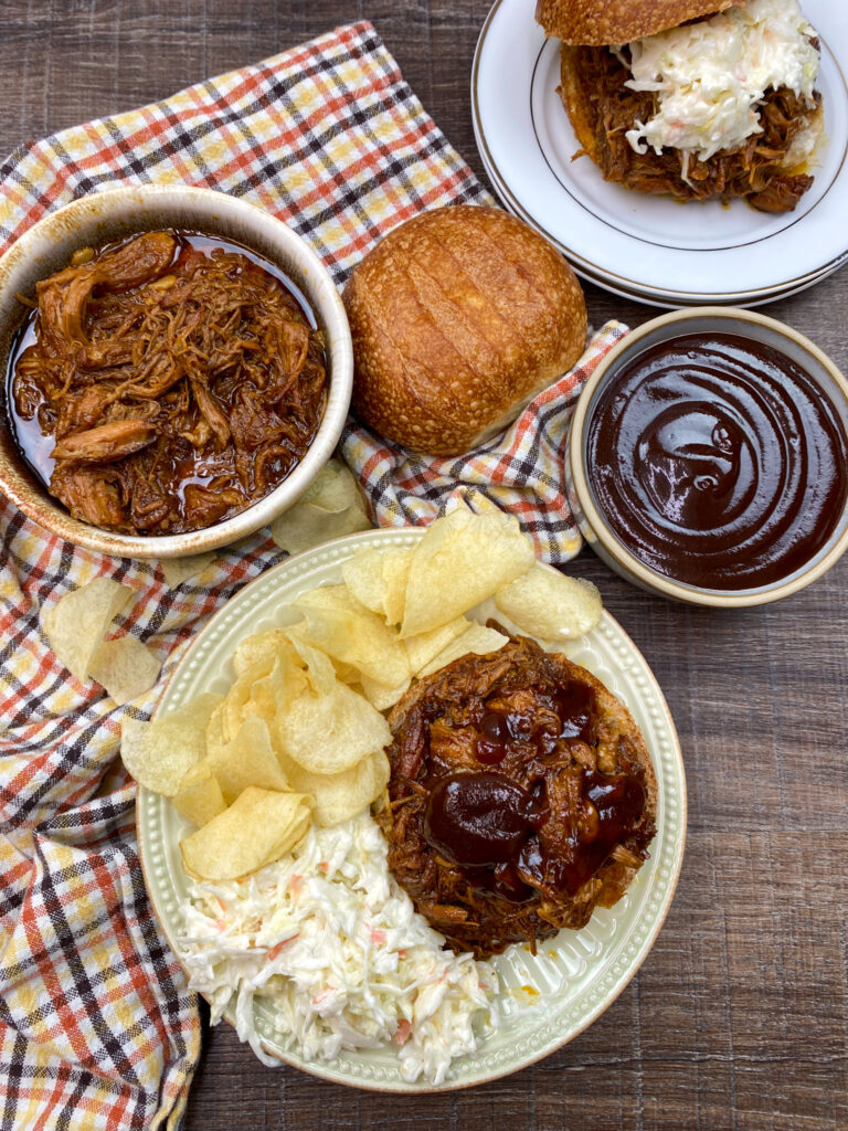 Pork sandwiches on a plate with chips, BBQ sauce, and coleslaw.