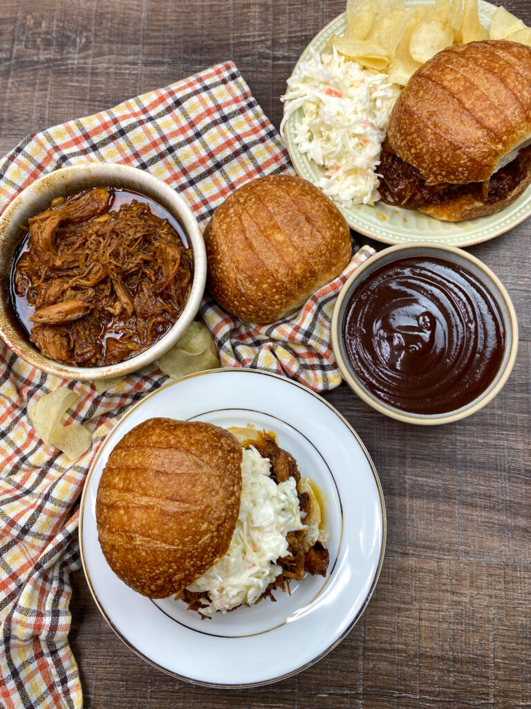 Pulled pork sandwiches on a white plate with coleslaw.