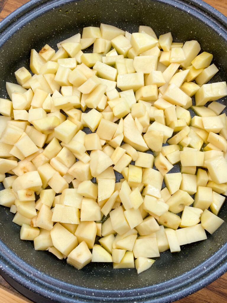 Diced potatoes with onion in a skillet.