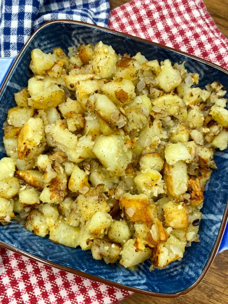 Southern fried potatoes and onions in a blue dish.