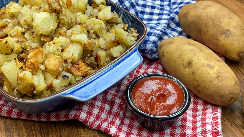 Golden brown potatoes in a blue dish.