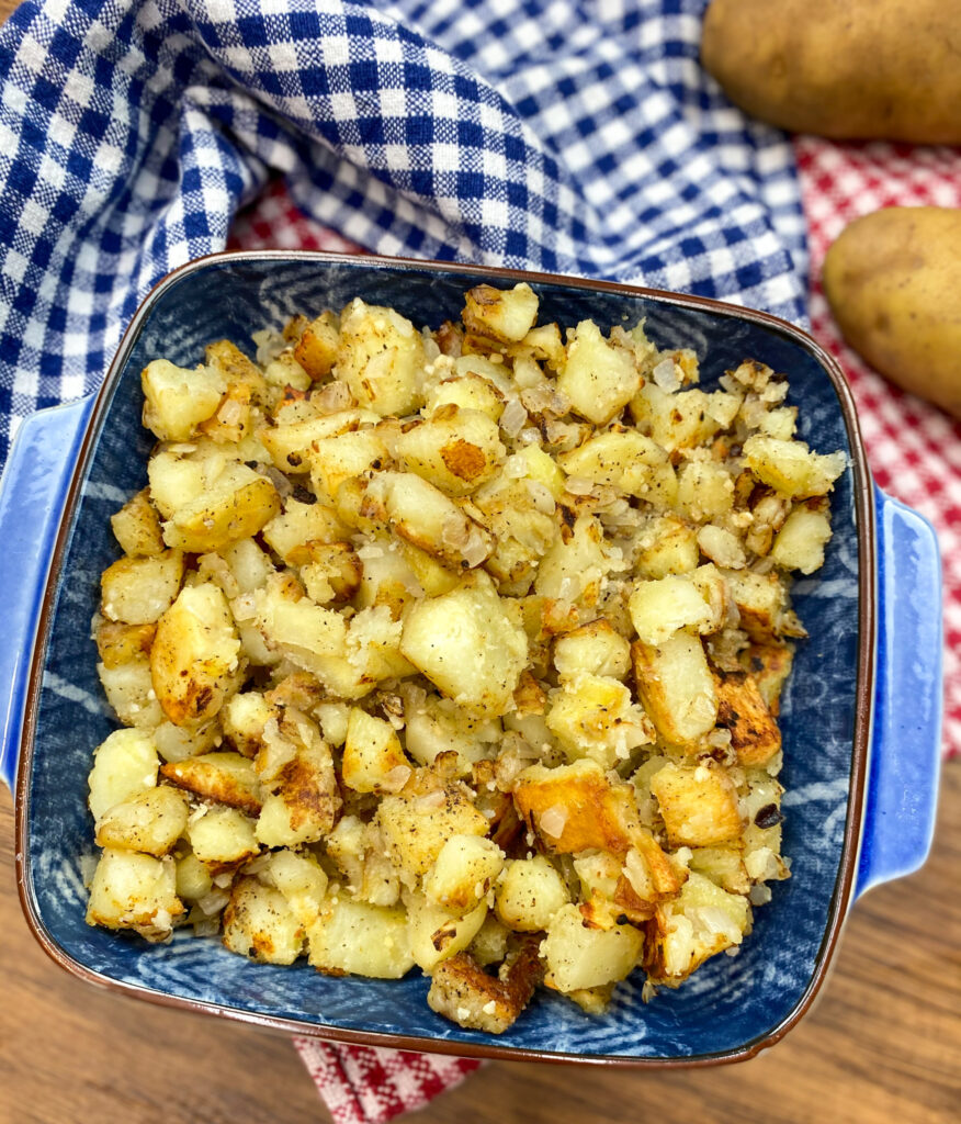 Diced and cooked home fries in a blue dish.