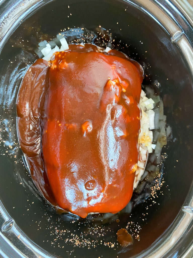 BBQ sauce on top of pork shoulder in the slow cooker.
