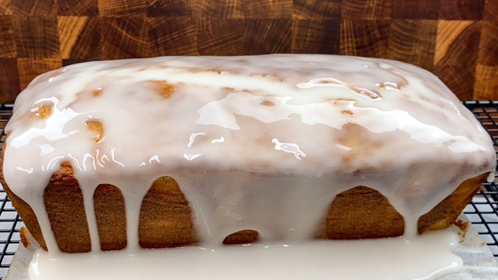 Pouring the lemon icing on top of lemon pound cake.