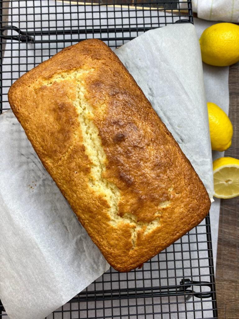 Baked lemon pound cake loaf on a cooling rack.
