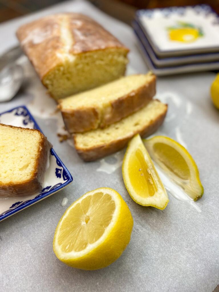 Lemon bread on parchment paper with lemons.
