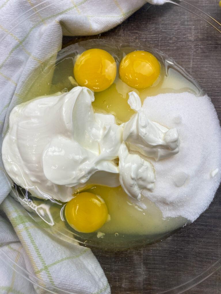Sour cream, eggs, and sugar in a bowl.