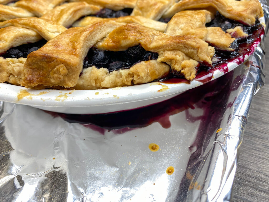Blueberry pie dripping over the sides onto a pan.
