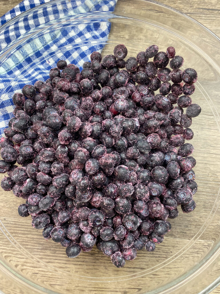 Frozen blueberries in a glass bowl.