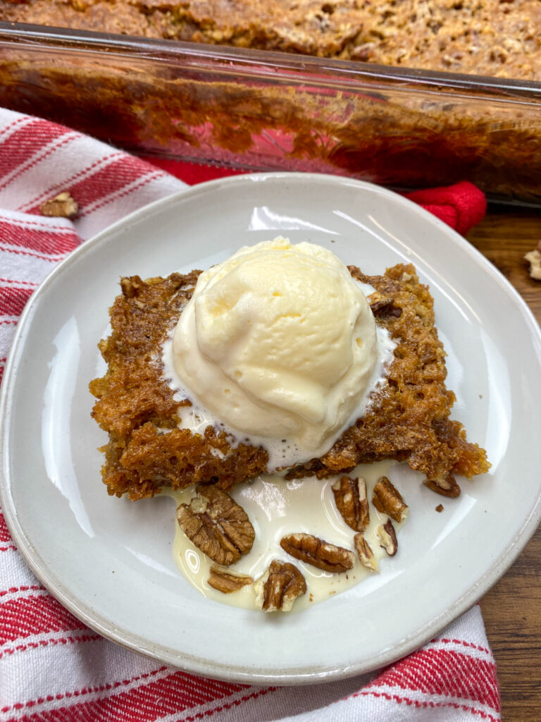 An ice cream scoop on top of pecan pie cake on a white plate.